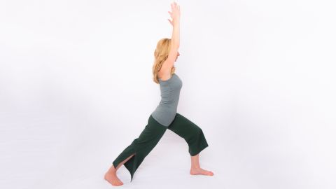 From standing, step back into a lunge but drop your back heel and point your toes out 45 degrees. Keep your back leg straight with your forward knee flexed above your ankle. Lift your arms overhead, shoulder-distance apart. Hold for five long, deep breaths. Repeat on the other side.