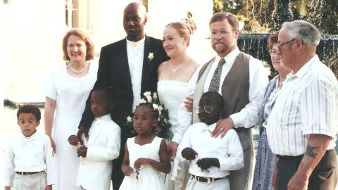 Rachel & Kevin's wedding reception in Jackson, MS on May 21, 2000.  We all went there for this event and to attend Rachel's college graduation from Belhaven College (now Belhaven University). I will list the people from left to right as you face the photo. Back row: Ruthanne (mother), Kevin & Rachel, Larry (father), Peggy & Herman (Larry's parents). Front Row, our adopted children: Ezra, Izaiah, Esther and Zachariah.