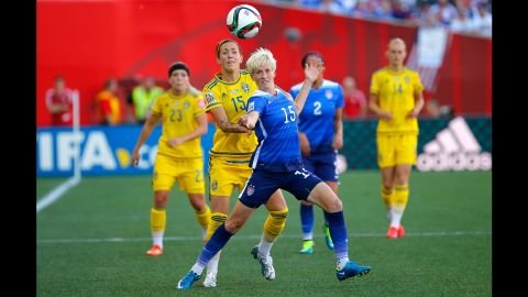 Rapinoe tries to hold off Sweden's Therese Sjogran.