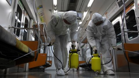 Workers wearing protective gear spray antiseptic solution in the subway amid rising public concerns over the spread of the MERS virus, on June 9, 2015, in Goyang, South Korea.