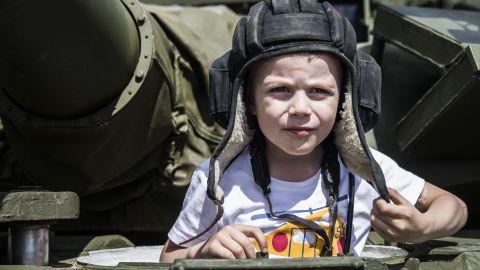 A boy plays on a tank.
