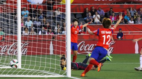 Hahnul Kwon and Younga Yoo celebrate as the ball goes into the net behind Spanish goalkeeper Ainhoa Tirapu.
