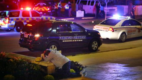 A man kneels across the street from where police gathered outside the church on June 17.