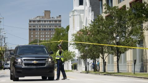 A police officer directs a police vehicle in front of the church on June 18.