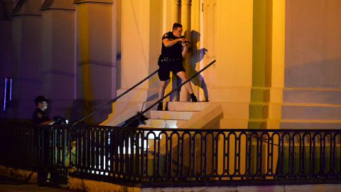 Charleston police officers search for the shooting suspect outside the church on Wednesday, June 17.