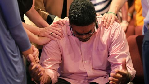 The Rev. Keith McDaniel, pastor of Macedonia Missionary Baptist Church, is surrounded by others in prayer on June 18 in Spartanburg, South Carolina.