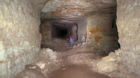 A member of the archaeological team sits inside the maze of burial tunnels in the catacombs of Anubis.