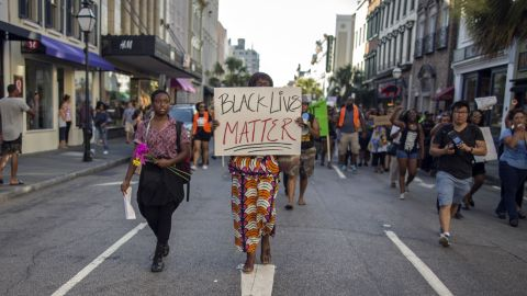 """Louise Brown walks down King Street during a """"Black Lives Matter"""" march on June 20 in Charleston, South Carolina."""