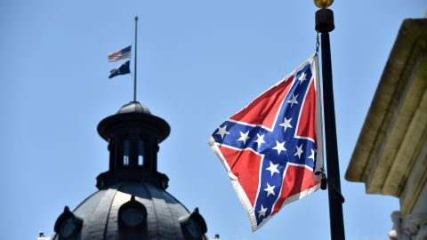The South Carolina and American flags flying at half-staff behind the Confederate flag erected in front of the State Congress building in Columbia, South Carolina on June 19, 2015. Police captured the white suspect in a gun massacre at one of the oldest black churches in Charleston in the United States, the latest deadly assault to feed simmering racial tensions. Police detained 21-year-old Dylann Roof, shown wearing the flags of defunct white supremacist regimes in pictures taken from social media, after nine churchgoers were shot dead during bible study on Wednesday.