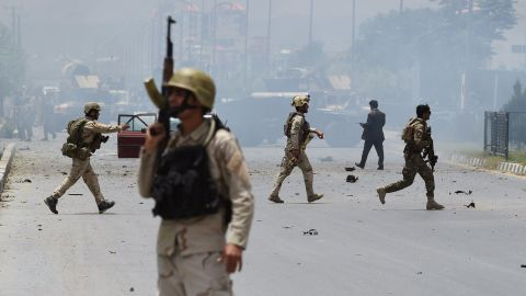 Afghan security personnel take position at the site of an attack in front of The Parliament Building in Kabul on June 22, 2015.