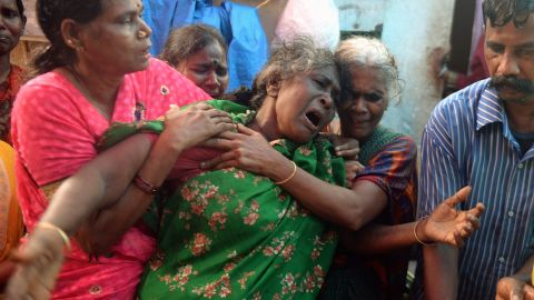 An Indian woman breaks down as she sees the dead body of a family member, a victim of toxic home-made liquor, in Mumbai.