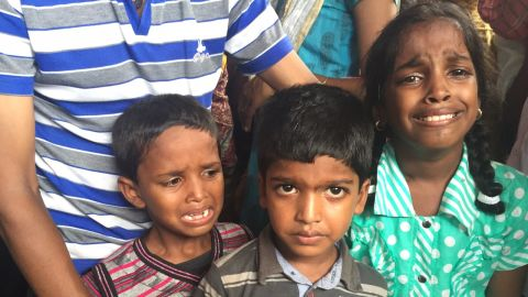 The three children of Satyavel Nagan Kawander, who died after drinking toxic moonshine, weep as their father's body is brought home.