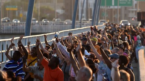 Thousands of people march on The Arthur Ravenel Jr. Bridge in Charleston, South Carolina on June 21, 2015.  People crossed the Bridge from Mount Pleasant and Charleston to join hands in a unity chain to mourn the 9 victims of the Emanuel AME Church shooting.