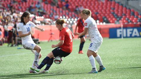 Norway forward Isabell Herlovsen, center, fights for the ball against England's Karen Carney, left.