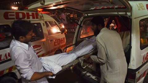 Relatives shift the dead body of a heatwave victim into an ambulance at the Edhi morgue in Karachi on June 21, 2015.