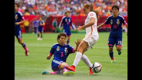 Japan's Azusa Iwashimizu knocks the ball away from Lieke Martens.