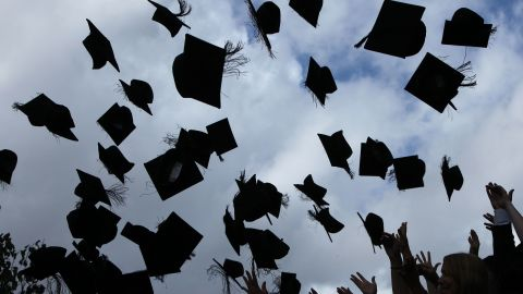 Students throw their caps in the air as they graduate