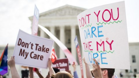 UNITED STATES - JUNE 25: Affordable Care Act supporters hold up signs outside the Supreme Court as they wait for the court's decision on Obamacare on Thursday, June 25, 2015. (Photo By Bill Clark/CQ Roll Call)