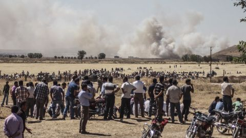"""Syrians wait near the Turkish border during clashes between ISIS and Kurdish armed groups in Kobani, Syria, on Thursday, June 25. The photo was taken in Sanliurfa, Turkey. ISIS militants disguised as Kurdish security forces infiltrated Kobani on Thursday and killed """"many civilians,"""" said a spokesman for the Kurds in Kobani."""