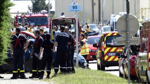 French police and firefighters gather at the entrance of the Air Products company in Saint-Quentin-Fallavier, near Lyon in central eastern France, on Friday, June 26, 2015. A suspected Islamist attacker pinned a severed head covered with Arabic writing to the gates of the gas factory, officials said. A suspect has been arrested and identified.