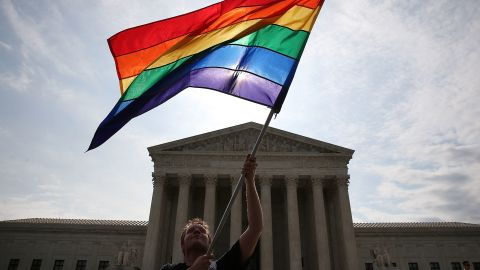A rainbow flag is waved in front of the Supreme Court in Washington.