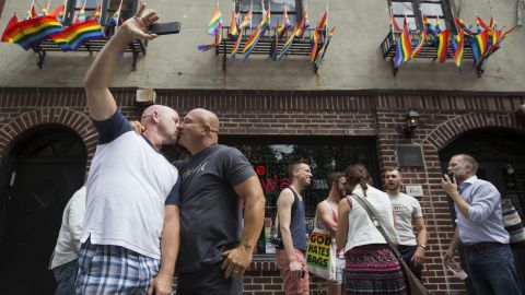 Doug Mest, left, and Mark Pelekakis kiss outside the Stonewall Inn in New York, the site of the 1969 Stonewall riots and an iconic bar in the LGBT community.