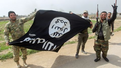 Members of Iraqi paramilitary Popular Mobilisation units, which are dominated by Shiite militias, celebrate with a flag of the Islamic State (IS) group after retaking the village of Albu Ajil, near the city of Tikrit, from the jihadist group, on March 9, 2015.