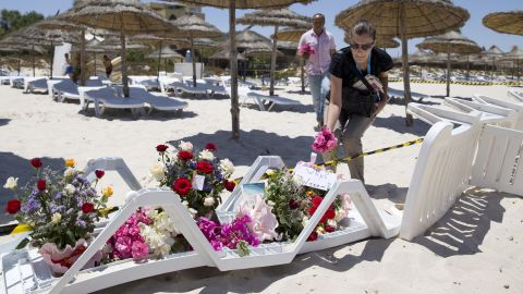 People lay flowers at the site of a shooting attack on the beach in front of the Riu Imperial Marhaba Hotel in Port el Kantaoui, on the outskirts of Sousse south of the capital Tunis, on June 27, 2015. The Islamic State (IS) group claimed responsibility on June 27 for the massacre in the seaside resort that killed nearly 40 people, most of them British tourists, in the worst attack in the country's recent history. AFP PHOTO / KENZO TRIBOUILLARD        (Photo credit should read KENZO TRIBOUILLARD/AFP/Getty Images)