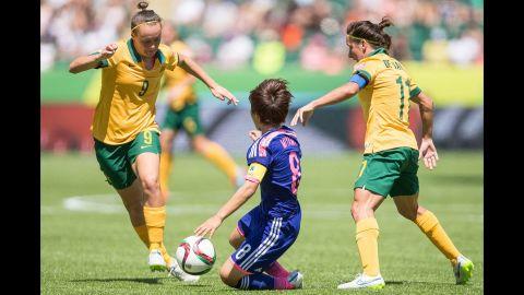 Australia's Caitlin Foord, left, and Lisa De Vanna try to keep the ball from Japan's Aya Miyama.