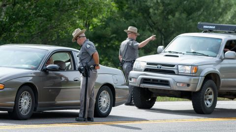 New York State Police officers talk to motorists at a roadblock near Malone on June 27.