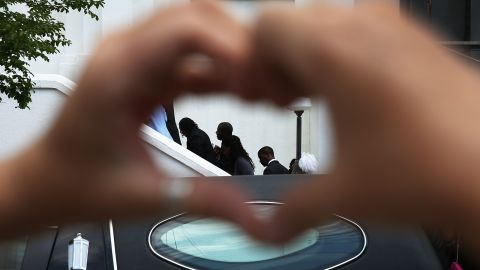 Heather Hayward forms a heart with her hands as mourners file in for the funeral of Cynthia Hurd, 54, at the Emanuel African Methodist Episcopal Church where she was killed along with eight others in a mass shooting at the church in Charleston, South Carolina.