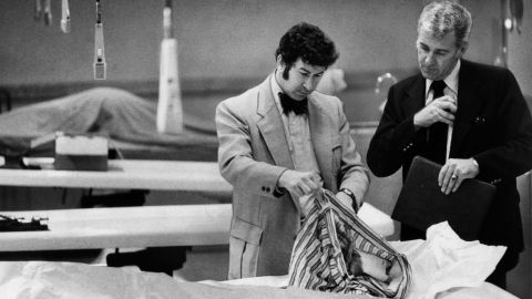 """Homicide inspectors David Toschi, left, and William Armstrong go through a """"Zodiac Killer"""" victim's clothes looking for clues. """"In the '70s there was a certain kind of killer who had the skill to get away with murder long enough to assemble the body count where they would be classified as serial killers,"""" said James Alan Fox, the author of """"Mass Killing."""" The Zodiac Killer has never been caught.<br />"""