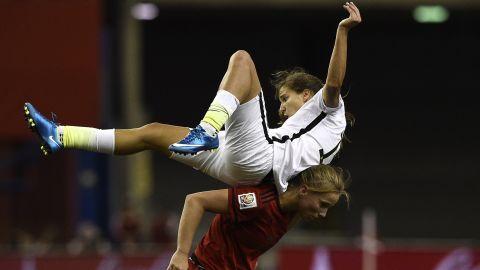 U.S. midfielder Tobin Heath gets knocked over by Germany's Tabea Kemme.