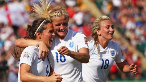 England's Katie Chapman, center, congratulates Fara Williams after Williams tied the score on a penalty kick. Both teams traded penalty-kick goals before Bassett's own goal.