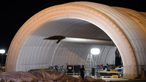 A mobile hangar is opened on Tuesday, June 23, as the plane is prepared for a possible takeoff.  The plane had been waiting in Japan for three weeks because of bad weather.