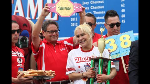 Miki Sudo holds her trophy after devouring four more hot dogs than she did last year and winning the annual Fourth of July competition.
