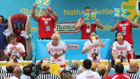 """The women's competition came down to Miki Sudo, second from left, and rival Sonya """"Black Widow"""" Thomas, second from right. Sudo won for the second straight year, eating 38 hot dogs."""