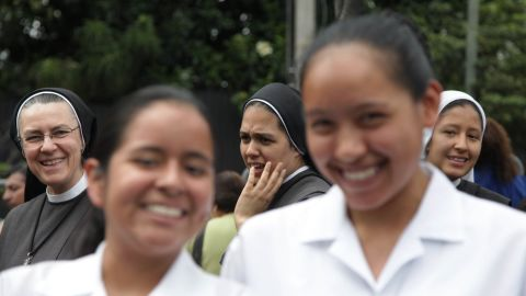 Nuns and faithful wait for Pope Francis to pass by after his arrival in Quito on July 5.