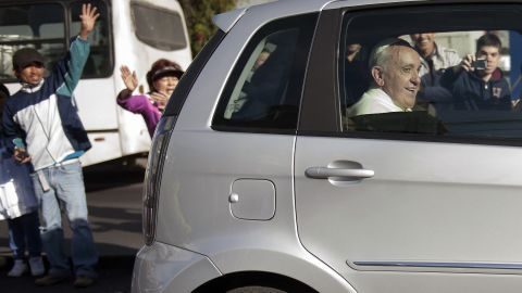 People wave as Pope Francis leaves the Apostolic Nunciature in Quito on July 6.