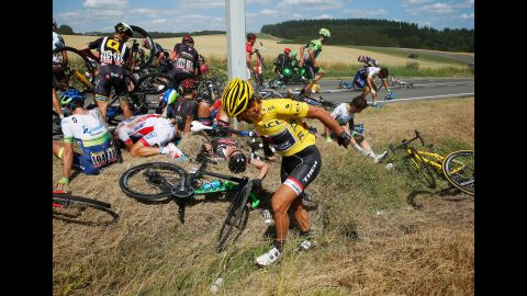"""Cyclists recover on the ground after <a href=""""http://bleacherreport.com/articles/2515851-huge-crash-takes-out-riders-on-stage-3-of-the-tour-de-france?utm_source=cnn.com&utm_medium=referral&utm_campaign=editorial"""" target=""""_blank"""" target=""""_blank"""">a massive crash</a> in the third stage of the Tour de France on Monday, July 6. The man in the foreground, Swiss cyclist Fabian Cancellara, was leading the race, but he had to withdraw after suffering two fractured vertebrae."""