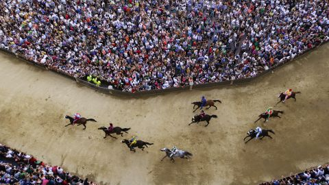 """A practice session is held Wednesday, July 1, for the Palio di Siena, a bareback horse race held twice a year in Siena, Italy. <a href=""""http://www.cnn.com/2013/08/26/sport/worlds-craziest-horse-festivals/index.html"""" target=""""_blank"""">The historic race</a> dates to the 17th century. Ten riders represent their local neighborhood as they race around the iconic city square three times."""