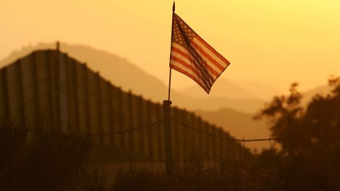 CAMPO, CA - OCTOBER 08:  A U.S. flag put up by activists who oppose illegal immigration flies near the US-Mexico border fence in an area where they search for border crossers October 8, 2006 near Campo, California. The activists want the fence expanded into a fully-lit double-fenced barrier between the US (R) and Mexico. US Fish and Wildlife Service wardens and environmentalists warn that a proposed plan by US lawmakers to construct 700 miles of double fencing along the 2,000-mile US-Mexico border, in an attempt to wall-out illegal immigrants, would also harm rare wildlife. Wildlife experts say cactus-pollinating insects would fly around fence lights, birds that migrate by starlight in the desert wilderness would be confused, and large mammals such as jaguars, Mexican wolves, Sonoran pronghorn antelope, and desert bighorn sheep would be blocked from migrating across the international border, from California to Texas.  (Photo by David McNew/Getty Images)