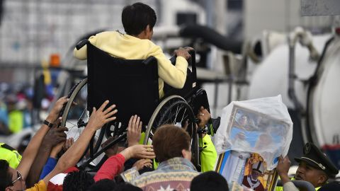 A disabled woman in Quito is lifted in a wheelchair during a Mass officiated by Pope Francis on July 7.