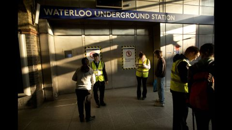 Workers from an outside agency give people travel advice by the closed entrance doors of the Waterloo Underground train station in London on July 9.