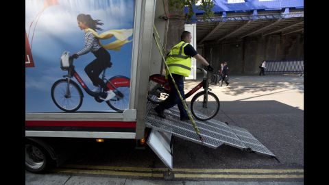 A man unloads bicycles to resupply a city bike-sharing station in London.