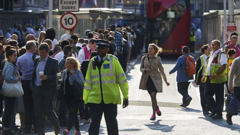 Early morning commuters form lines to board buses at Victoria Station.