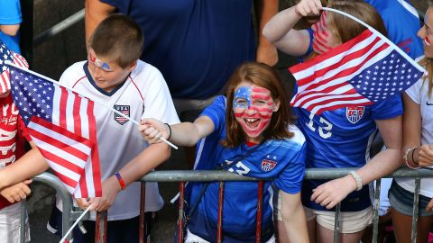 A young fan cheers while waiting for the ticker tape parade, the first in New York for a women's sports team.
