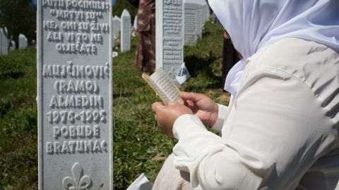 A Bosnian women prays at the grave of a relative in Srebrenica cemetery.