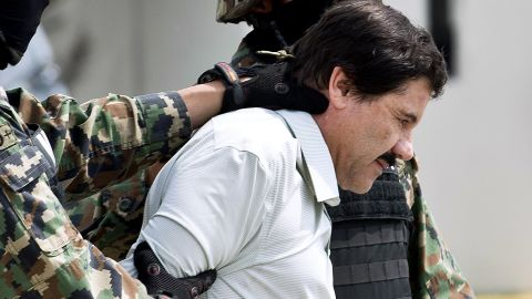 """Joaquin """"El Chapo"""" Guzman is escorted by marines as he is presented to the press on February 22, 2014, in Mexico City."""