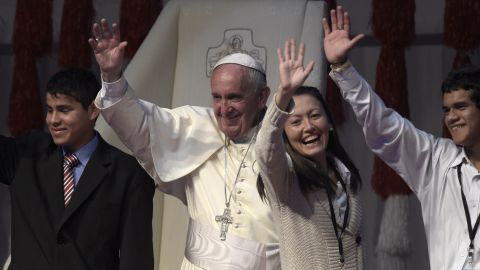 """Pope Francis waves during a meeting with young people at the """"Costanera"""" in Asuncion, Paraguay, on Sunday, July 12, the final day of his eight-day tour of South America."""